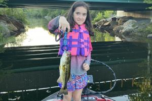 Young girl holding a river bass