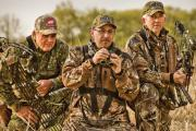 3 Bow Hunters dressed in camo standing together with binoculars scouting prey