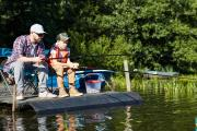 Father & son fishing from a boat dock by Father & son fishing from a boat dock...
