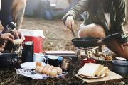 Two campers preparing breakfast food at a campsite over a fire